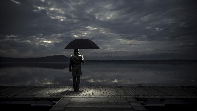дощатый причал, мужчина под зонтиком, озеро, далекий берег, хмурое небо с пробивающимися лучами солнца, легкая грусть, настроение