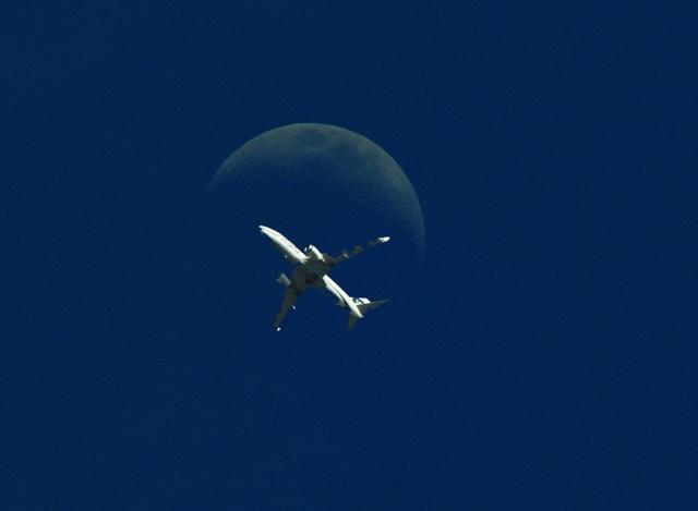 літак у польоті, на тлі місяця, загальний фон темно-синій, мінімалізм