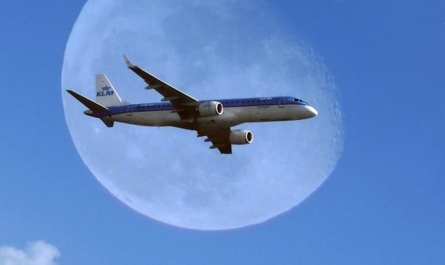 самолет в полете, на фоне луны, общий фон светло-синий, минимализм