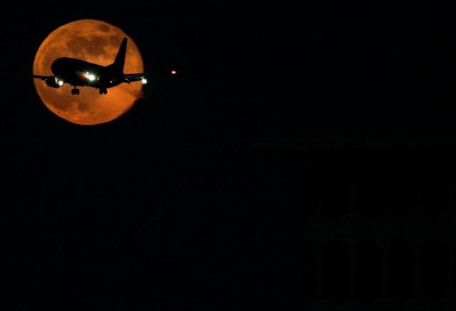 самолет идущий на посадку, на фоне луны, общий фон черный