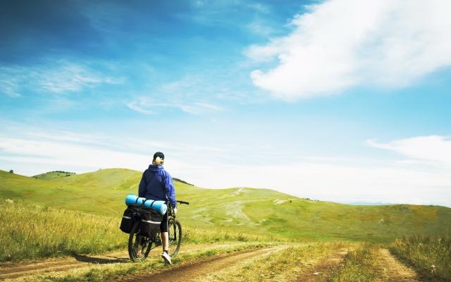 tourist, bike, dirt road, green field