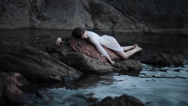 дівчина, спить, на камені