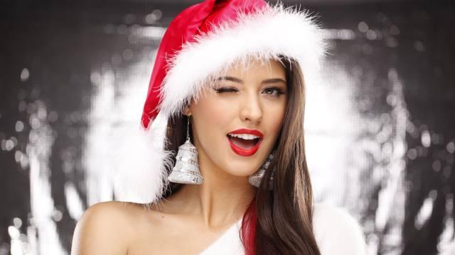 красива дівчина, брюнетка, в новогоднем костюме, подмигивает глазом