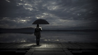 wooden pier, the man under the umbrella, the lake, distant shore, gloomy sky with piercing rays of the sun, sad, mood
