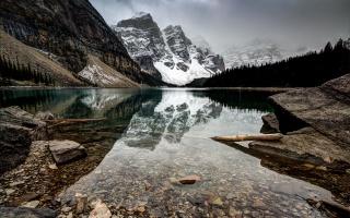 Чорне озеро в горах, корчі, каміння, снігові гори, туман