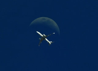 the plane in flight, on the background of the moon, the General background of dark blue, minimalism