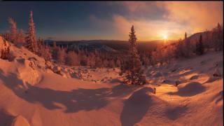Заснеженный склон холма, поросший деревьями, на фоне заката в горах, tapety na plochu pro desktop